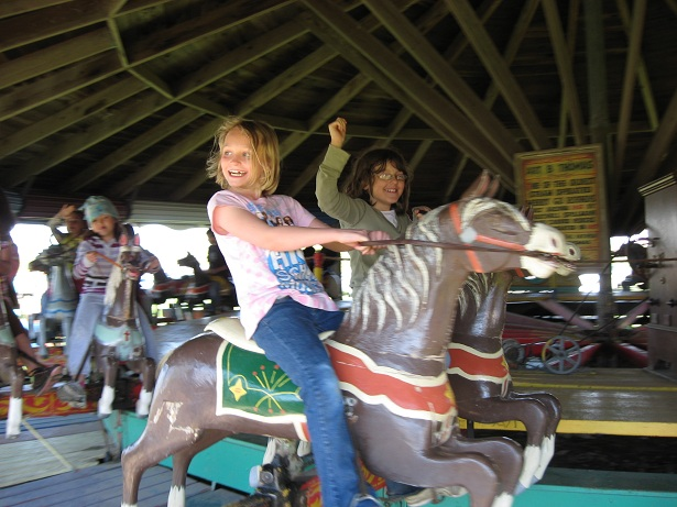 Smiling young ladies riding on carousel horses.